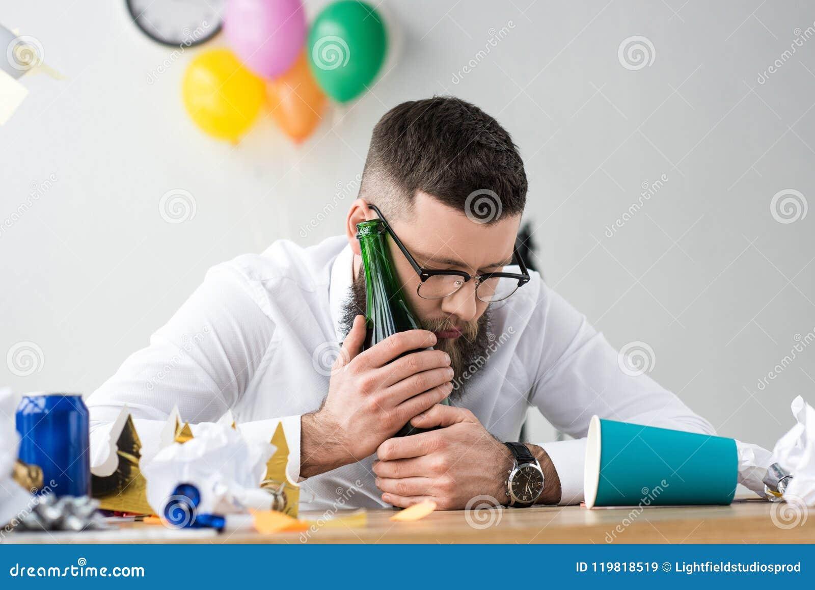 Homem de negócios bêbado com a garrafa do champanhe no local de trabalho