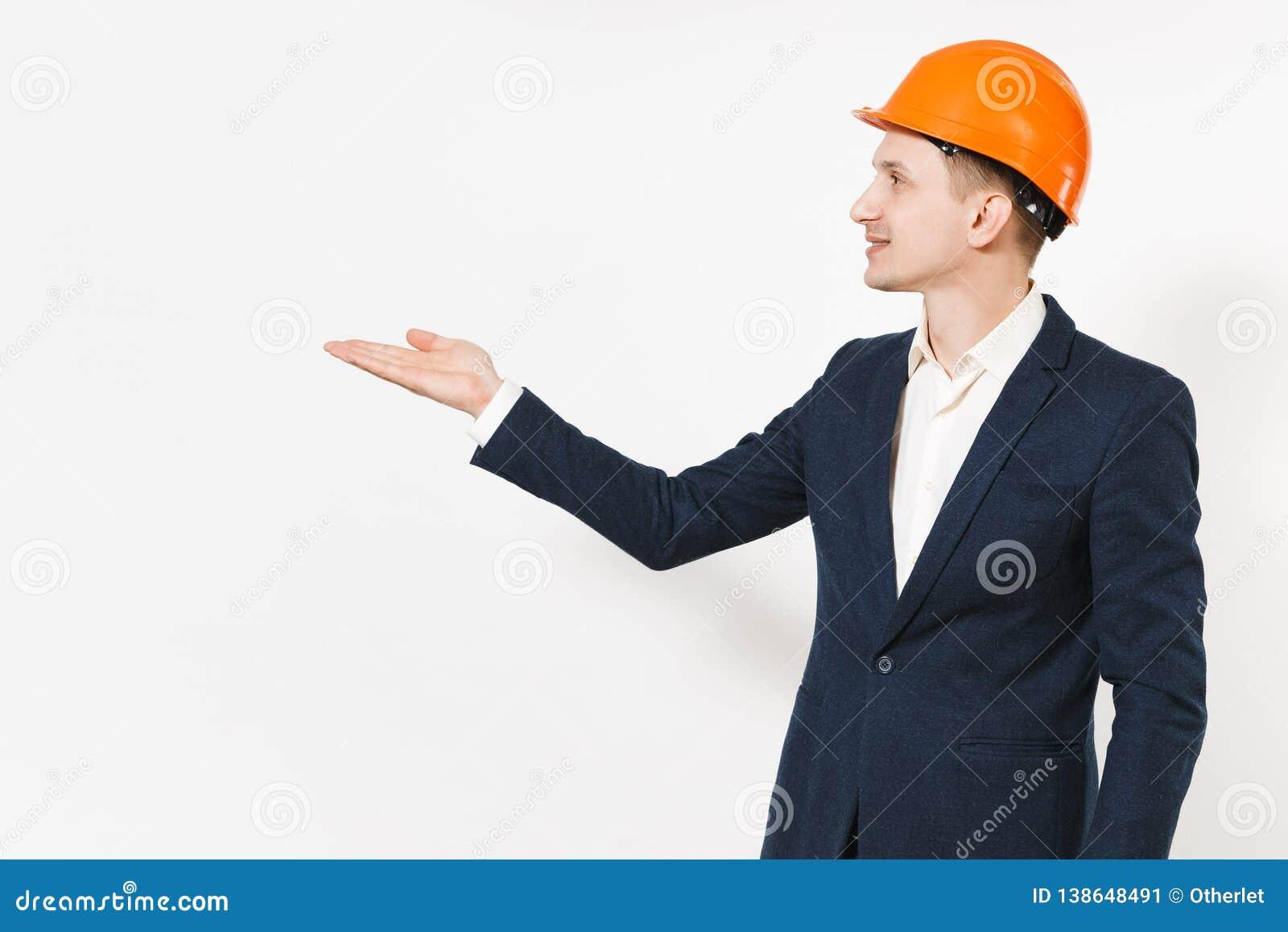 Homem de negócios bem sucedido considerável novo no terno escuro, capacete de segurança protetor apontando a mão de lado no espaç