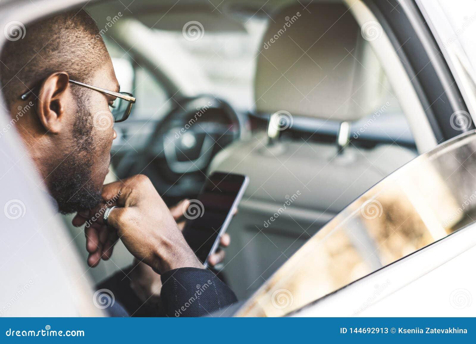 Homem de negócios bem sucedido novo que fala no telefone que senta-se no assento traseiro de um carro caro Negociações e negó