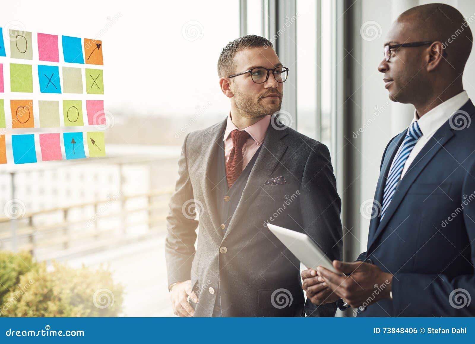 Homem de negócios caucasiano e africano em uma reunião