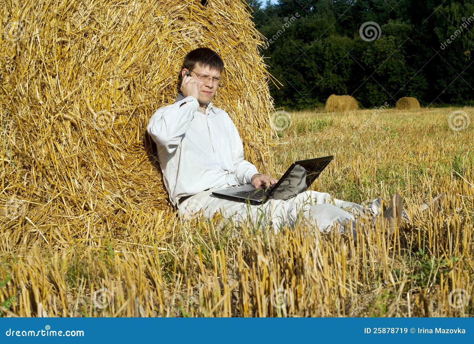 Homem de negócios com o portátil perto dos monte de feno
