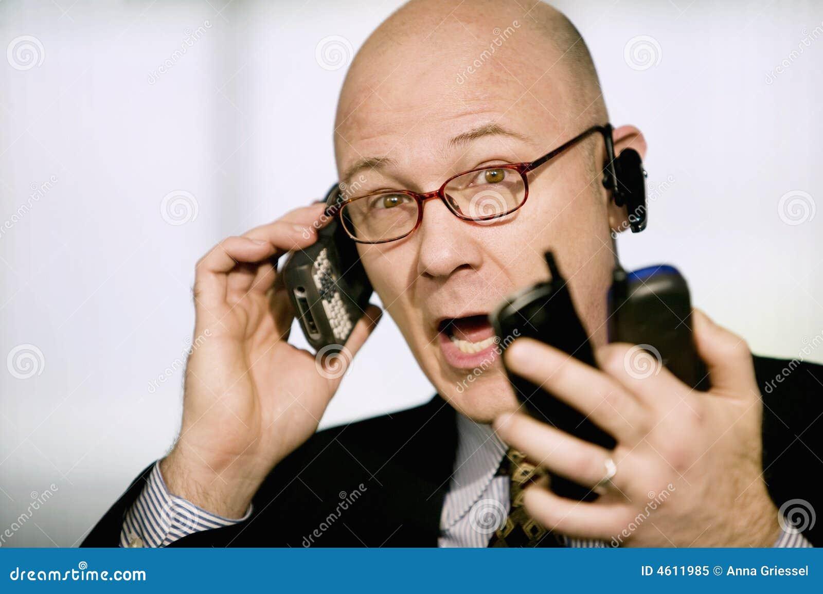 Homem de negócios com os telefones de pilha múltiplos