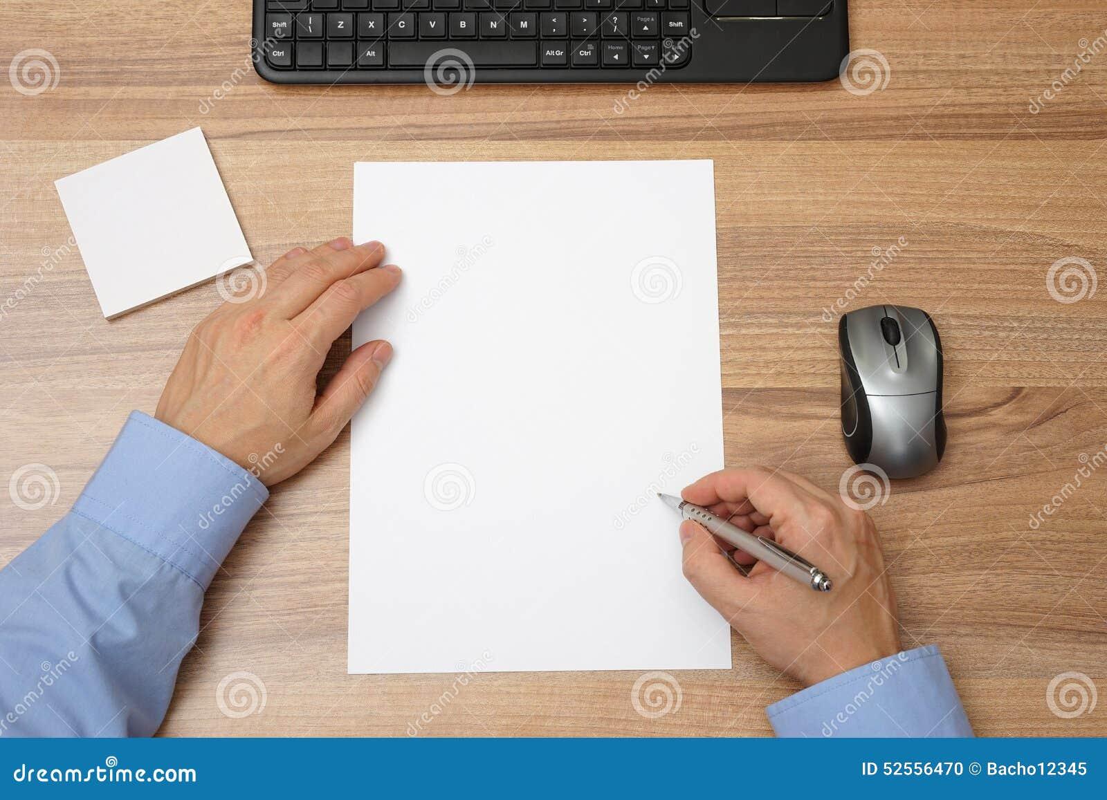 Homem de negócios com papel vazio e pena à disposição a começar com o wri
