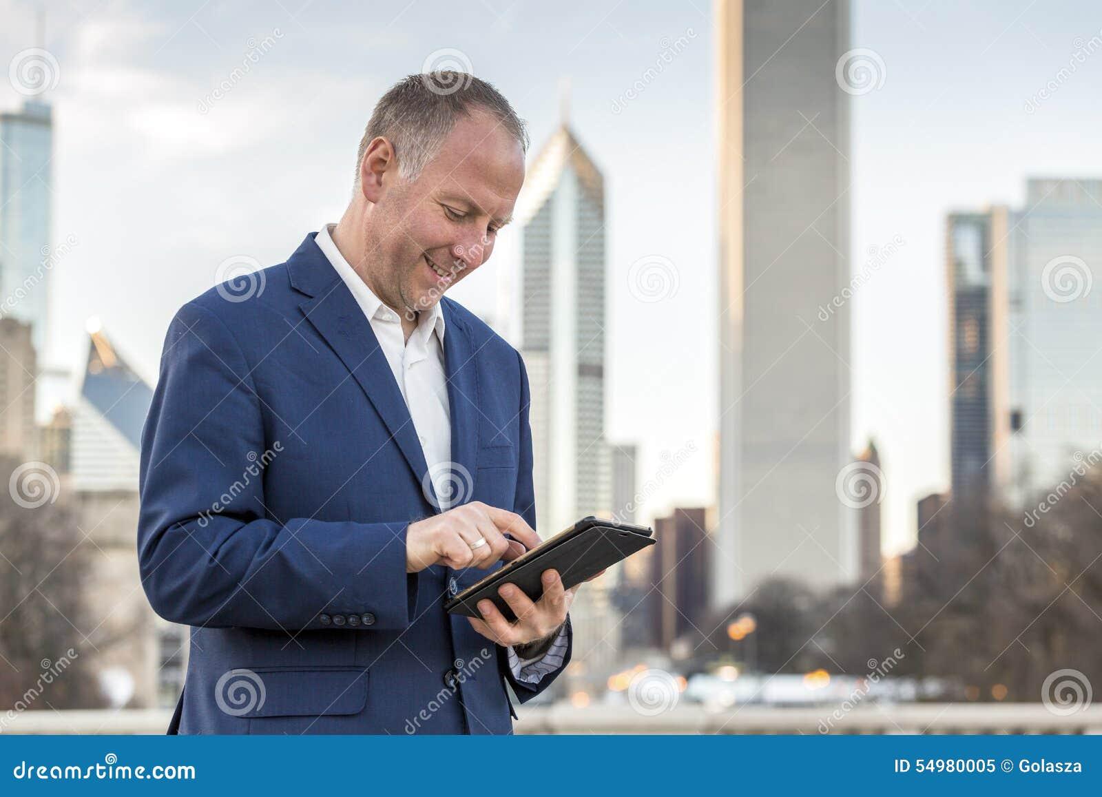 Homem de negócios com a tabuleta na frente dos prédios de escritórios