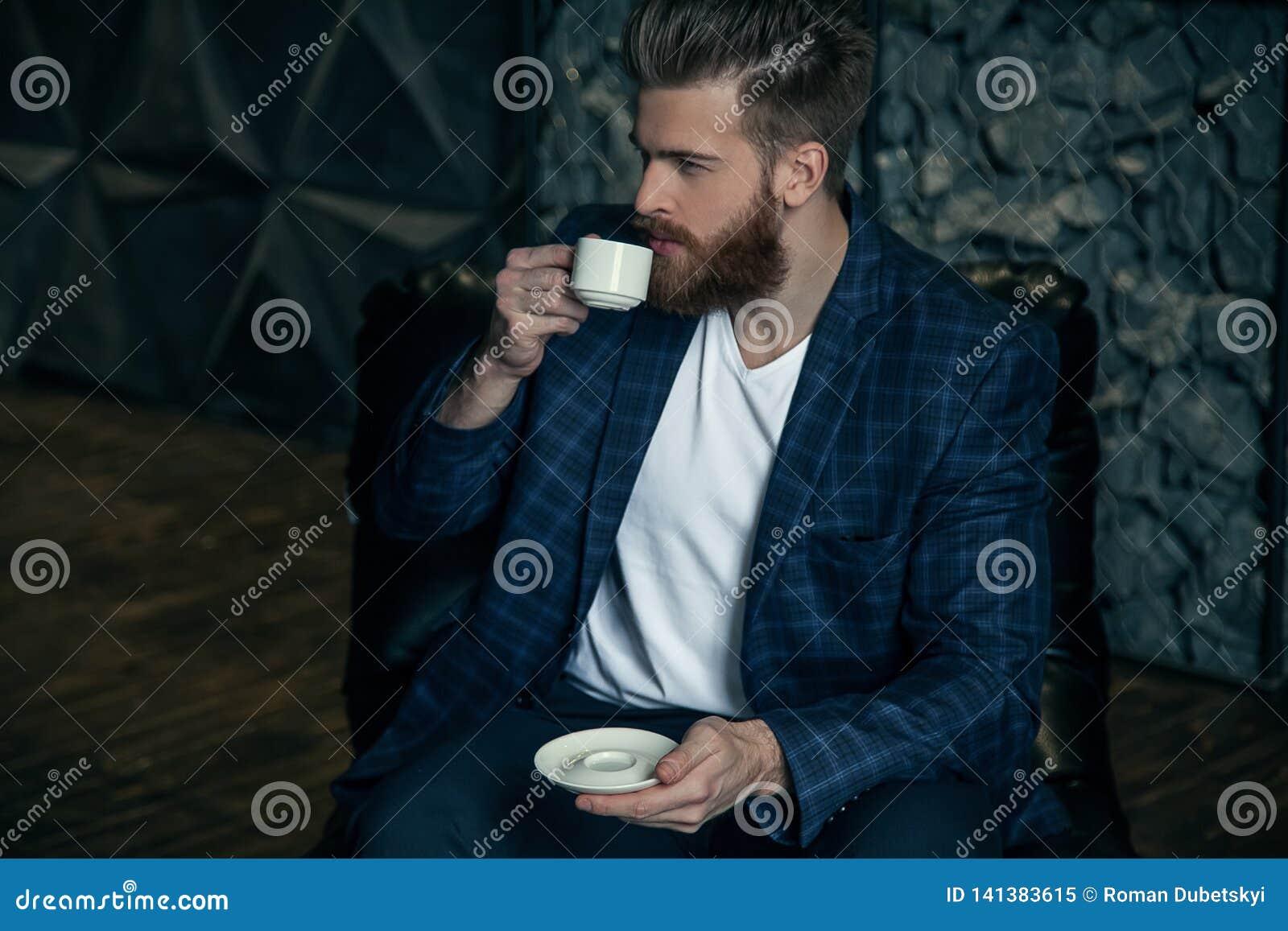 Homem de negócios com a xícara de café que situa contra do fundo moderno