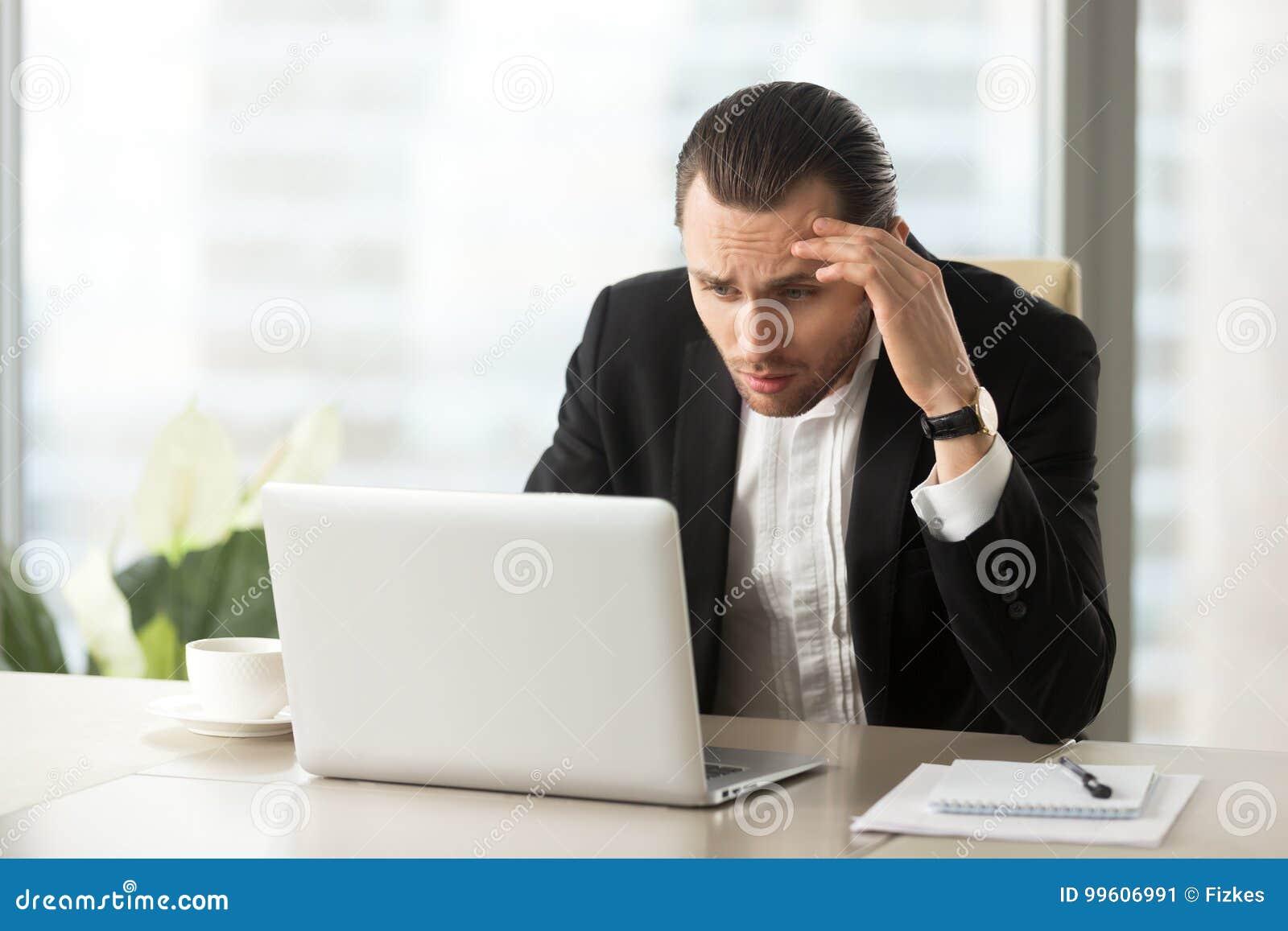 Homem de negócios confuso virado que olha a tela do portátil no local de trabalho