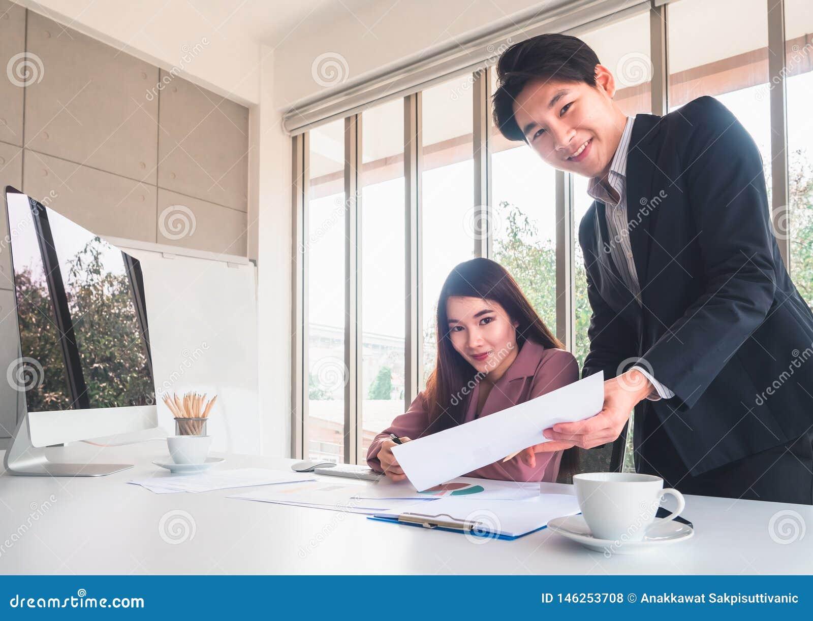Homem de negócios considerável asiático para explicar detalhes do trabalho à mulher de negócios bonita