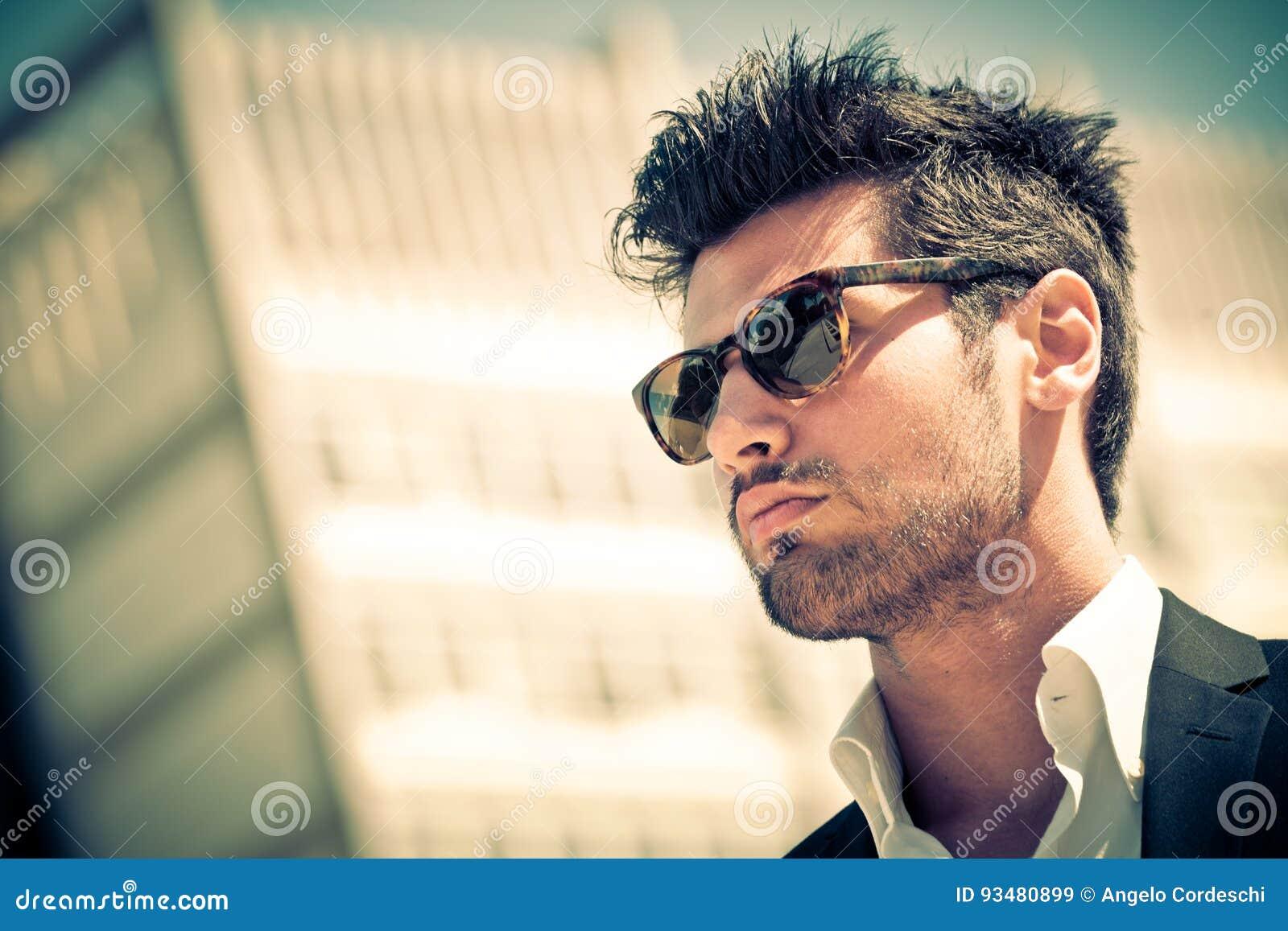 Homem de negócios considerável com óculos de sol