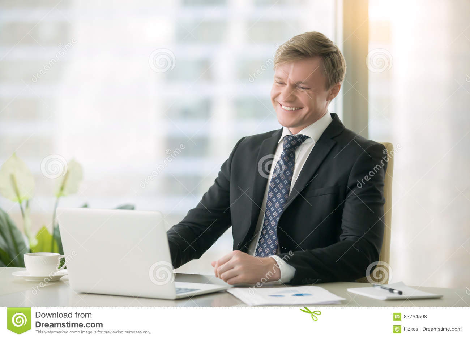 Homem de negócios considerável de sorriso com portátil