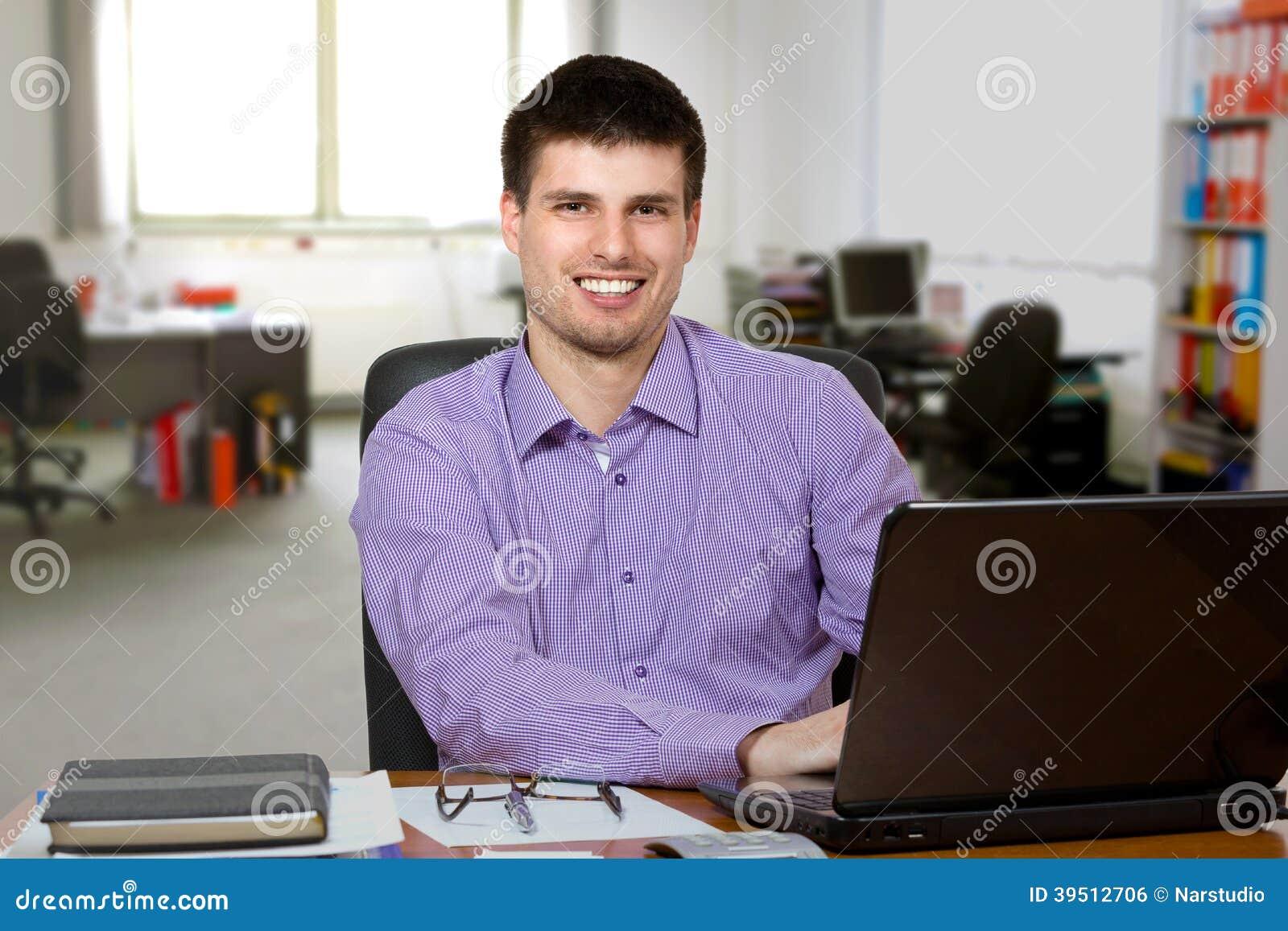 Homem de negócios considerável novo que trabalha no portátil