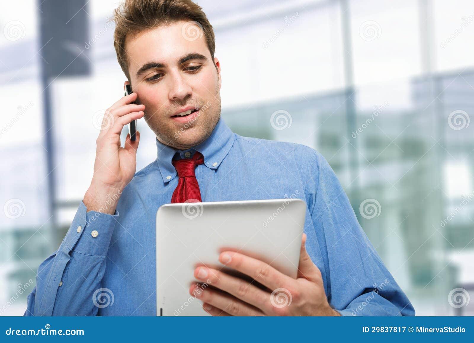 Homem de negócios novo que fala no telefone