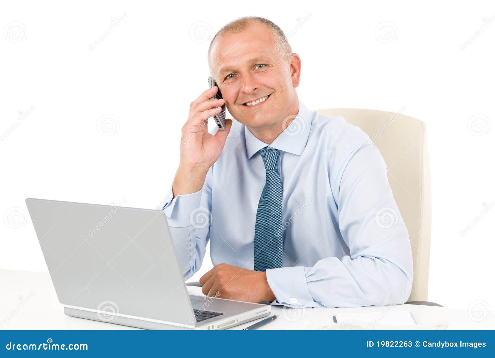 Homem de negócios de sorriso que senta-se no escritório atrás da mesa