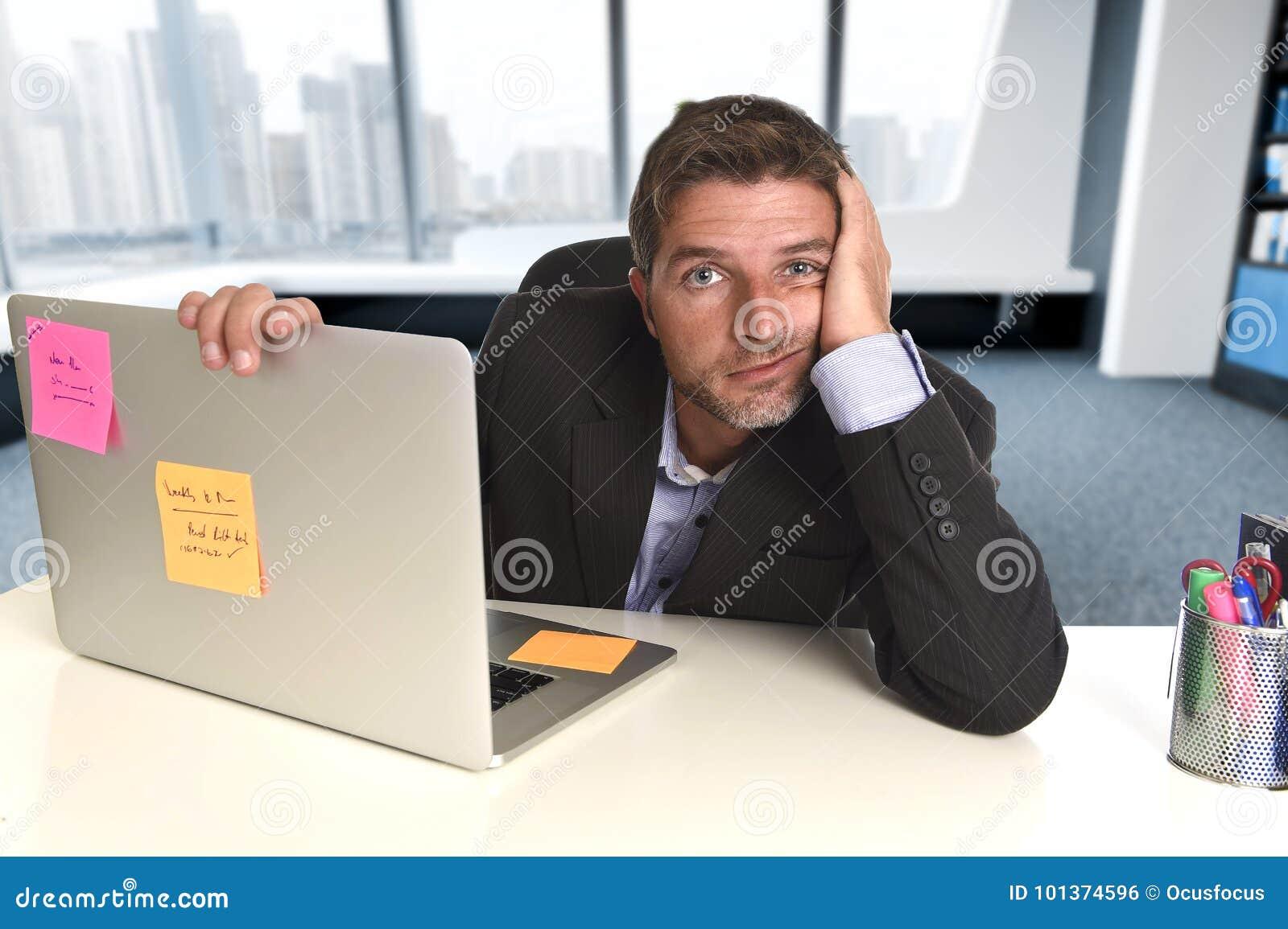 Homem de negócios desperdiçado que trabalha no esforço no laptop do escritório que olha esgotado