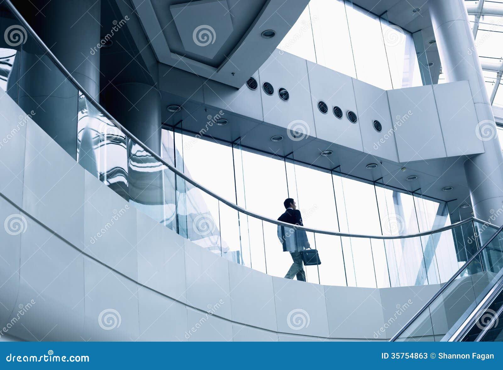 Homem de negócios distante que anda em um prédio de escritórios moderno