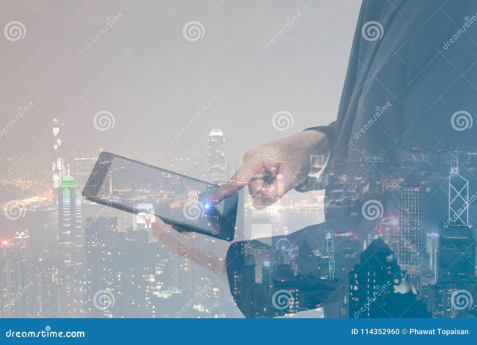 Homem de negócios do conceito da exposição dobro que veste o terno preto e que trabalha com uma tabuleta digital com fundo modern