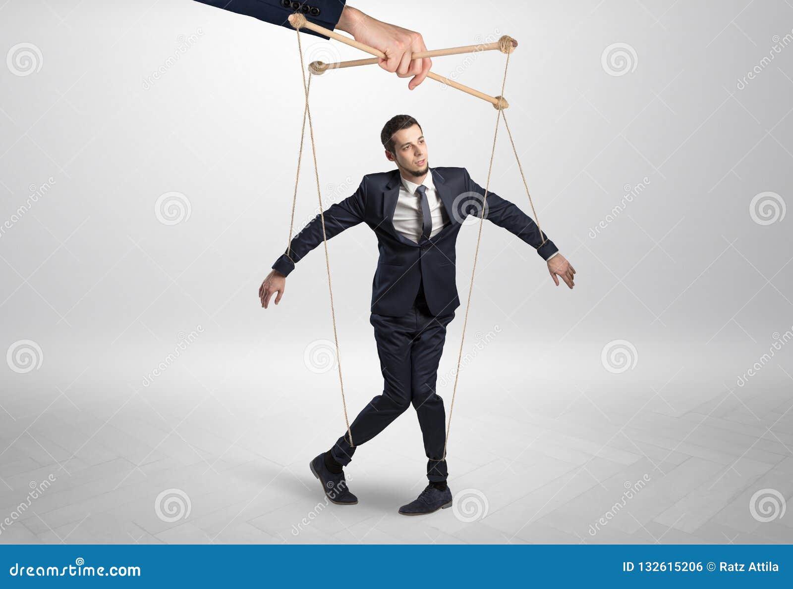 Homem de negócios do fantoche leaded por uma mão enorme