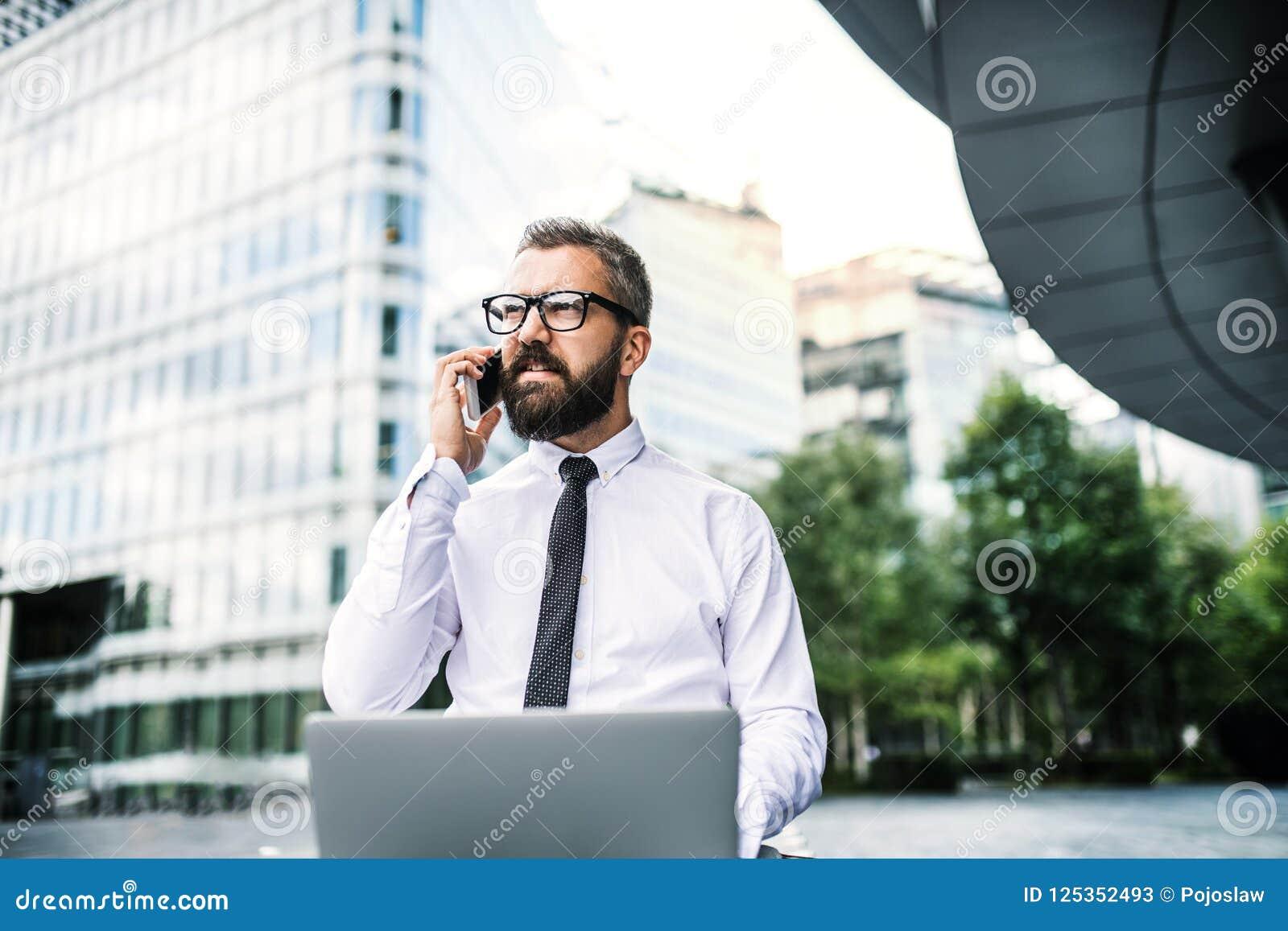 Homem de negócios do moderno com portátil e smartphone na cidade