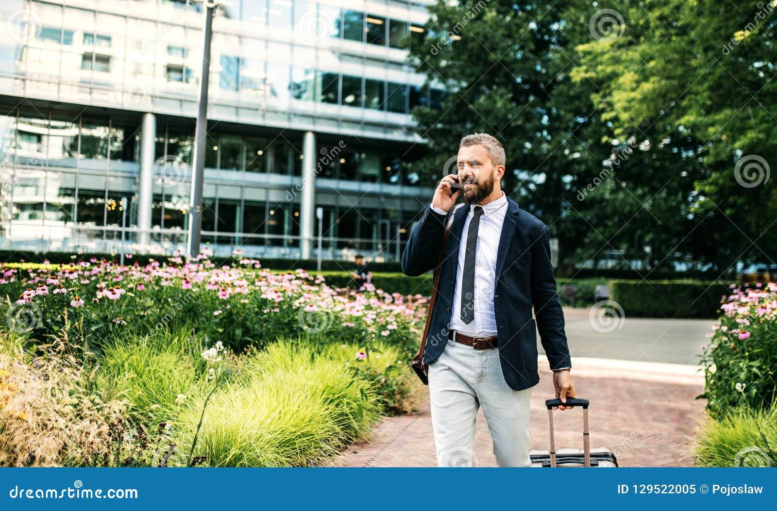 Homem de negócios do moderno com smartphone e mala de viagem que anda no parque em Londres