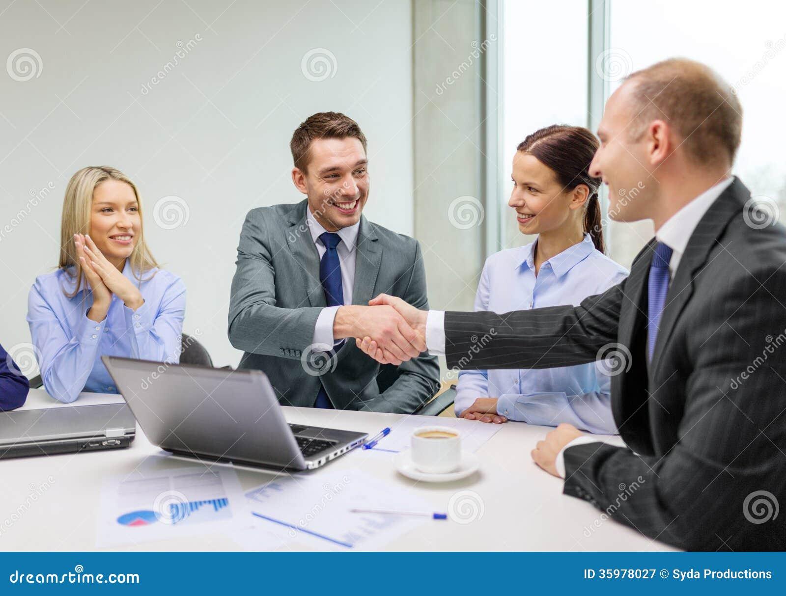 Homem de negócios dois que agita as mãos no escritório