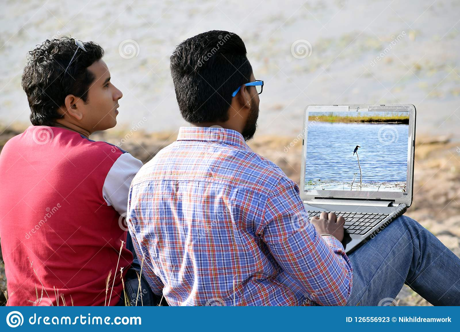 Homem de negócios dos jovens dois que usa o portátil em exterior