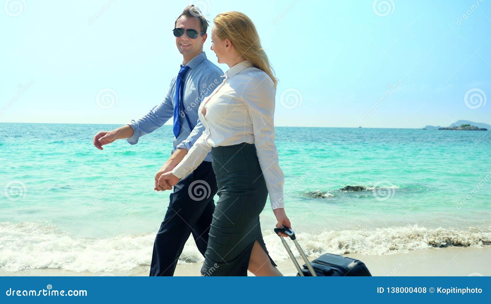 Homem de negócios e mulher de negócio com uma mala de viagem que anda ao longo da praia branca da areia na ilha