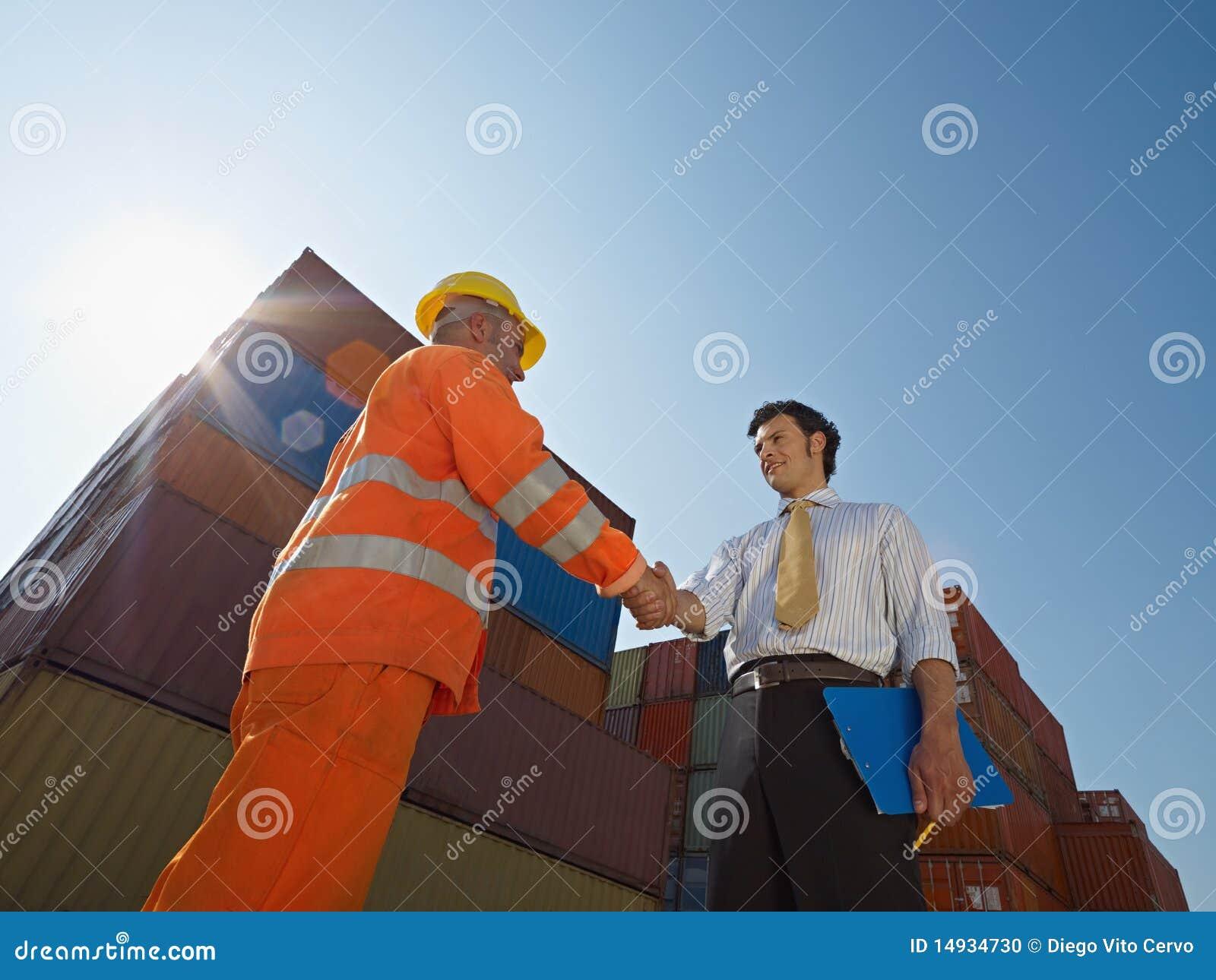 Homem de negócios e trabalhador com recipientes de carga