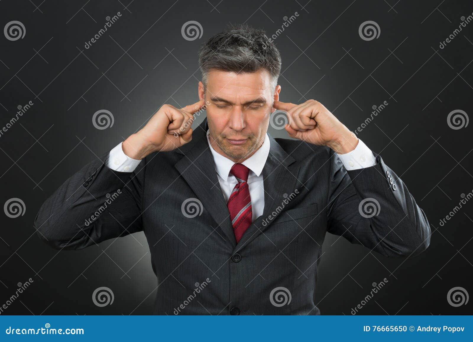Homem de negócios With Eyes Closed e dedos em suas orelhas