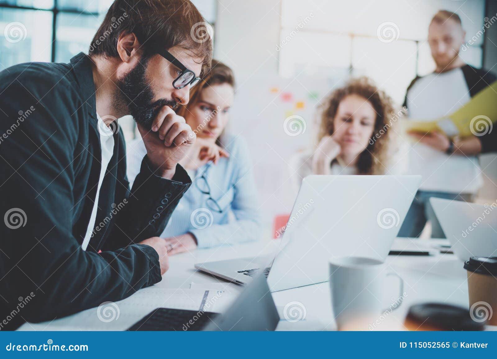 Homem de negócios farpado com a equipe do negócio que faz a conversação na sala de reunião ensolarada horizontal Fundo borrado