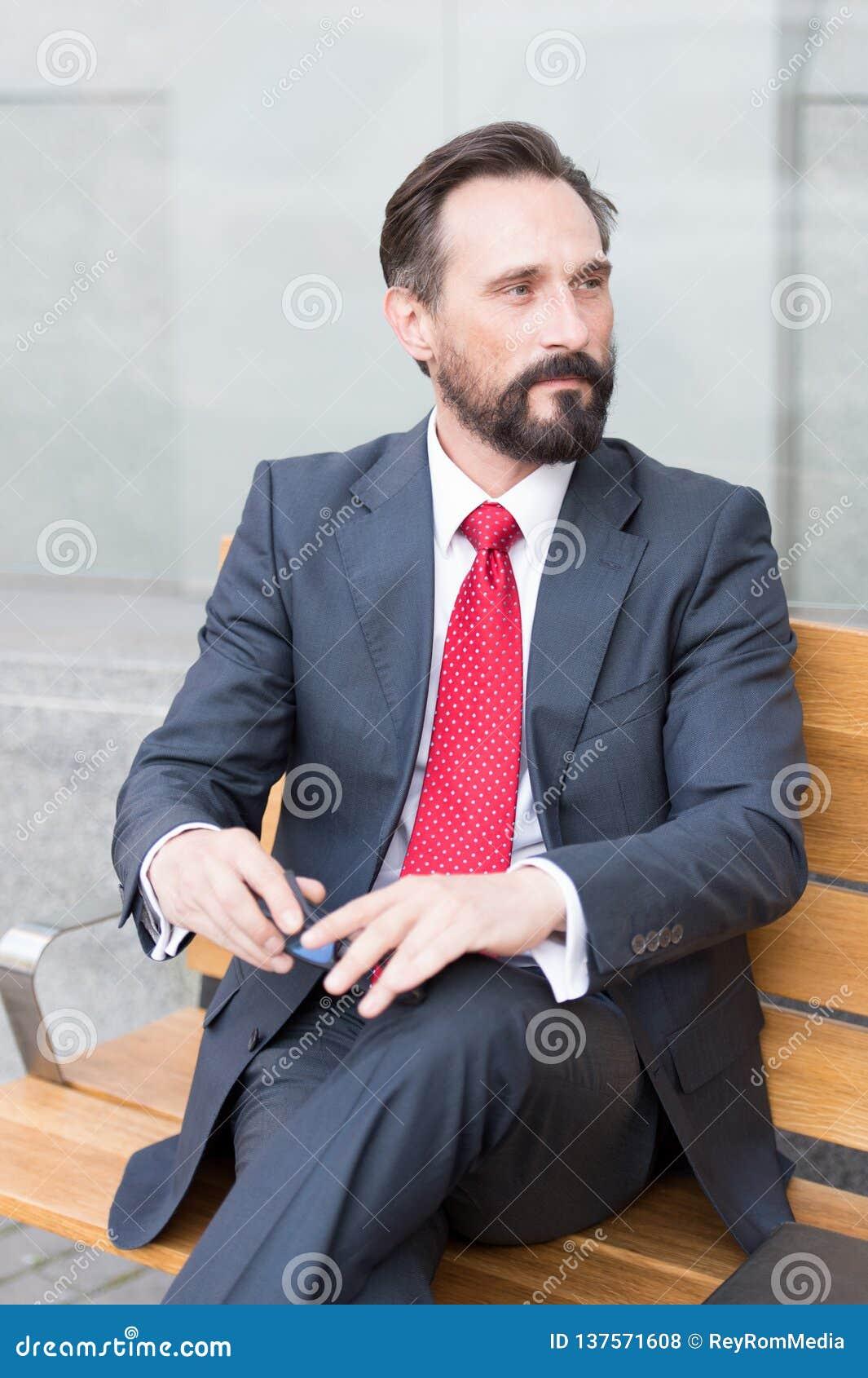 Homem de negócios farpado pensativo que olha afastado ao descansar no banco