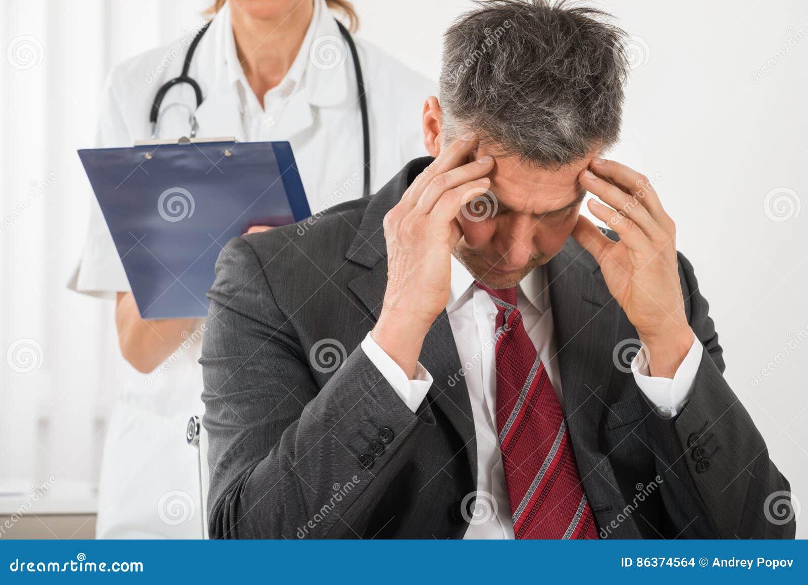 Homem de negócios Having Headache do doutor Standing Behind The