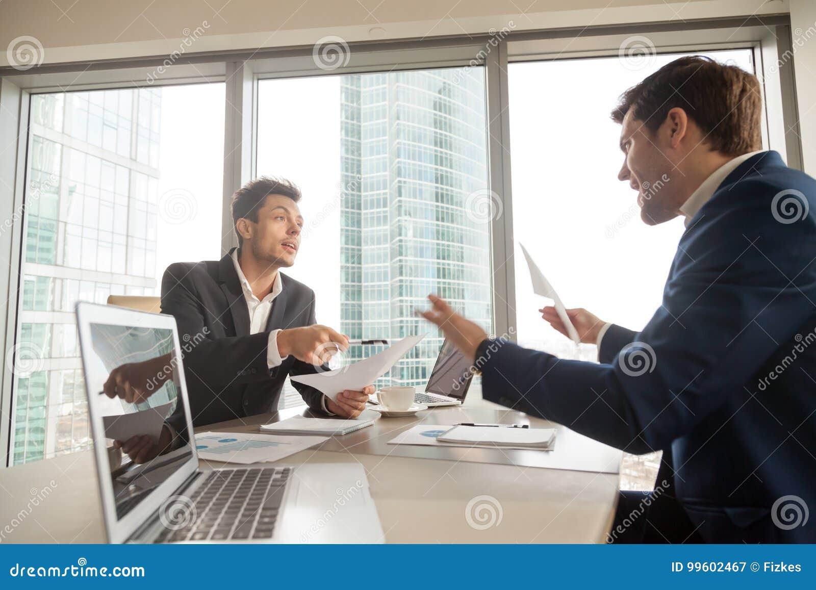 Homem de negócios irritado que discute com o sócio na reunião