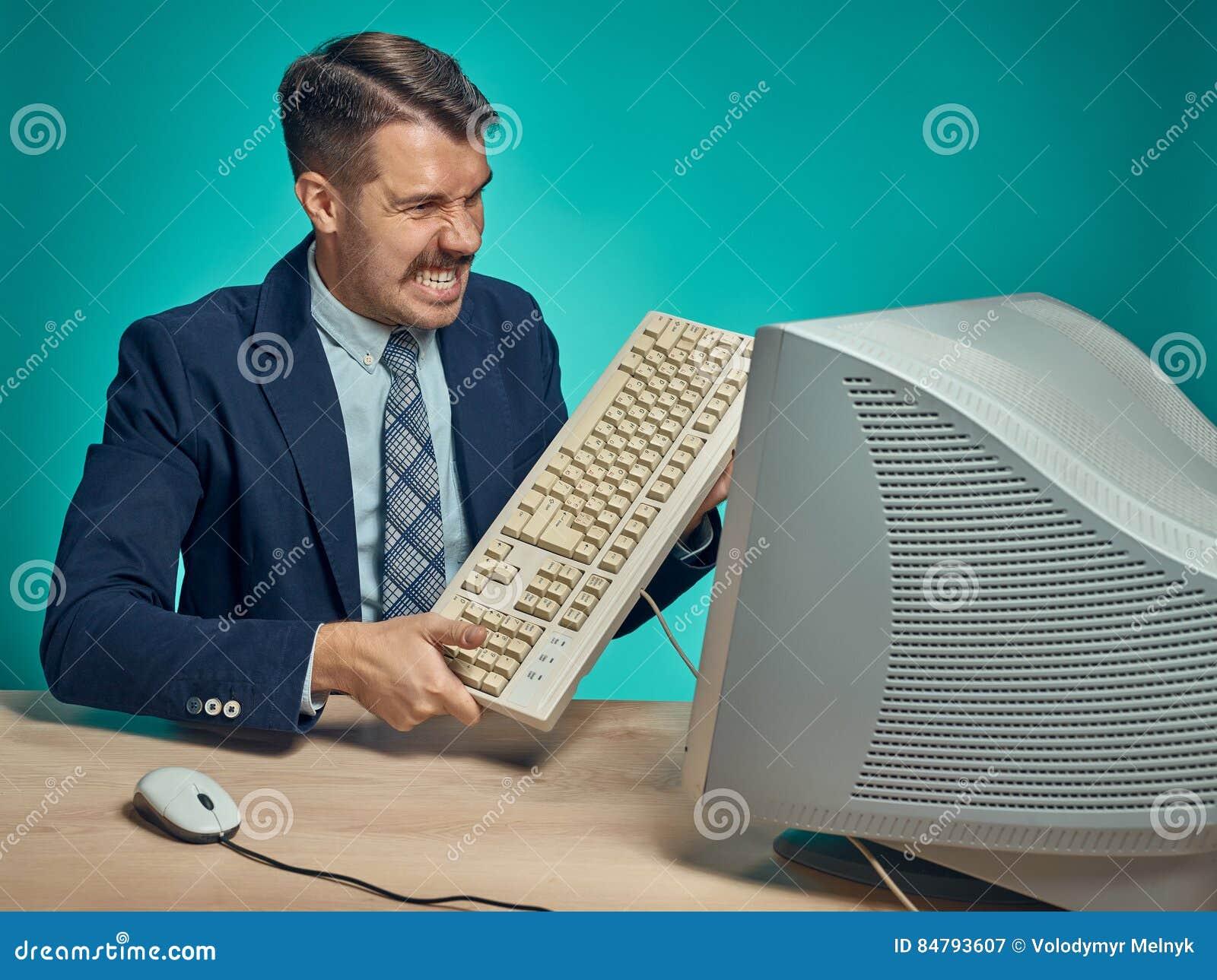 Homem de negócios irritado que quebra o teclado contra o fundo azul
