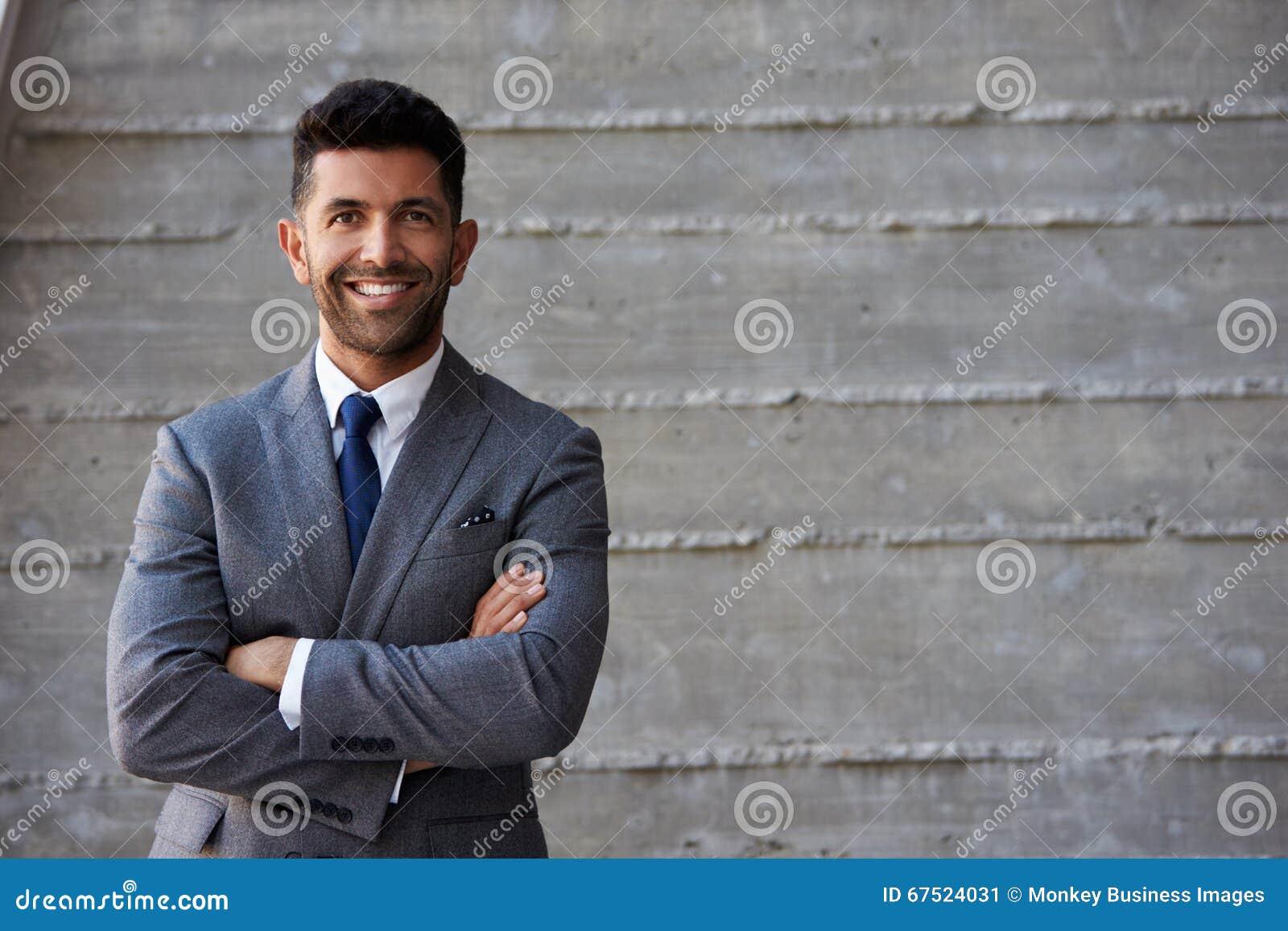 Homem de negócios latino-americano Standing Against Wall no escritório moderno