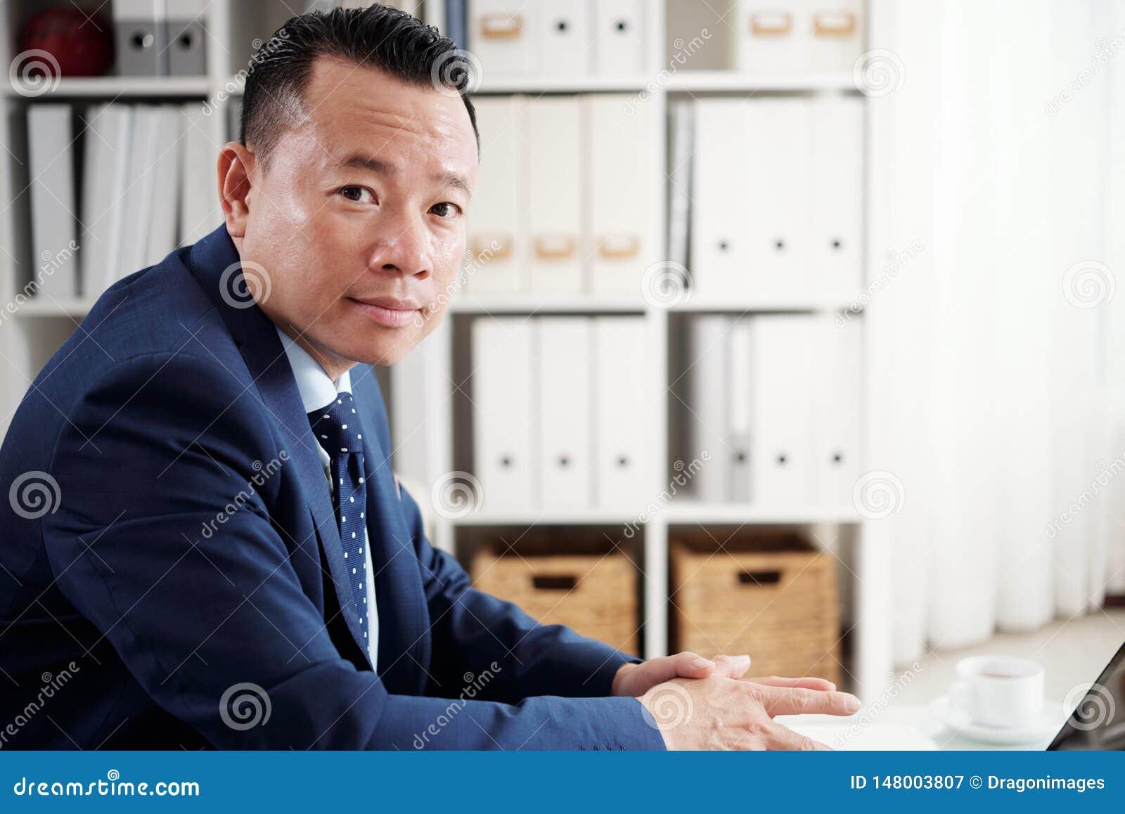 Homem de negócios maduro asiático que trabalha no escritório