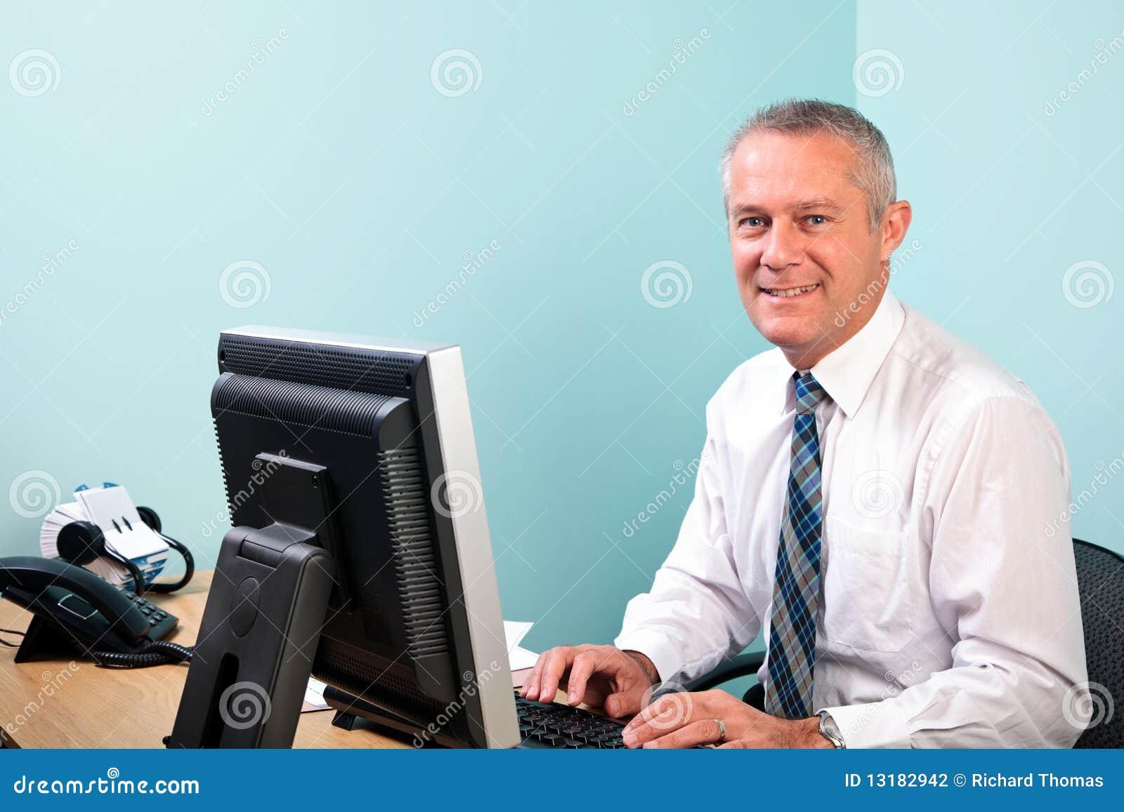 Homem de negócios maduro sentado em sua mesa de escritório