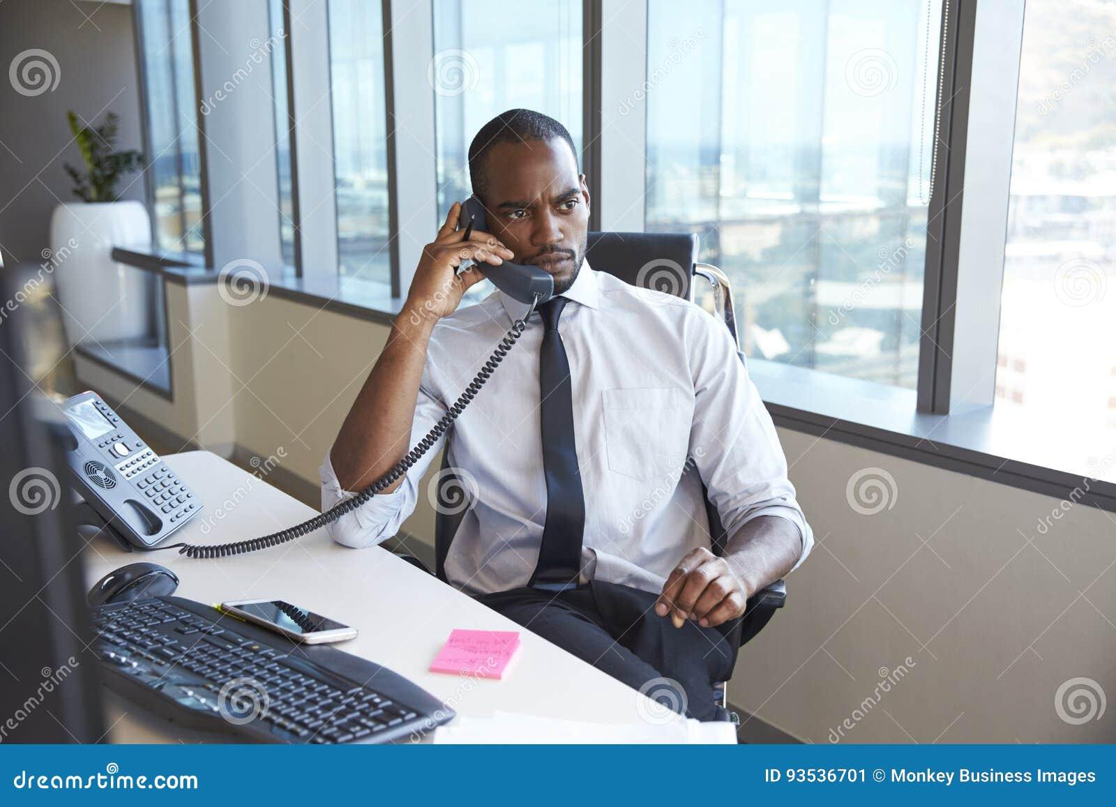Homem de negócios Making Phone Call que senta-se na mesa no escritório