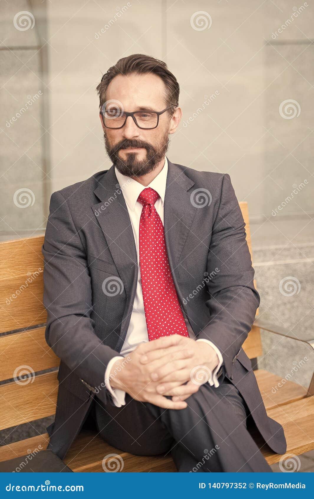 Homem de negócios de meia idade que toma uma ruptura de relaxamento no banco Série da vida urbana de pessoas do negócio Retrato d