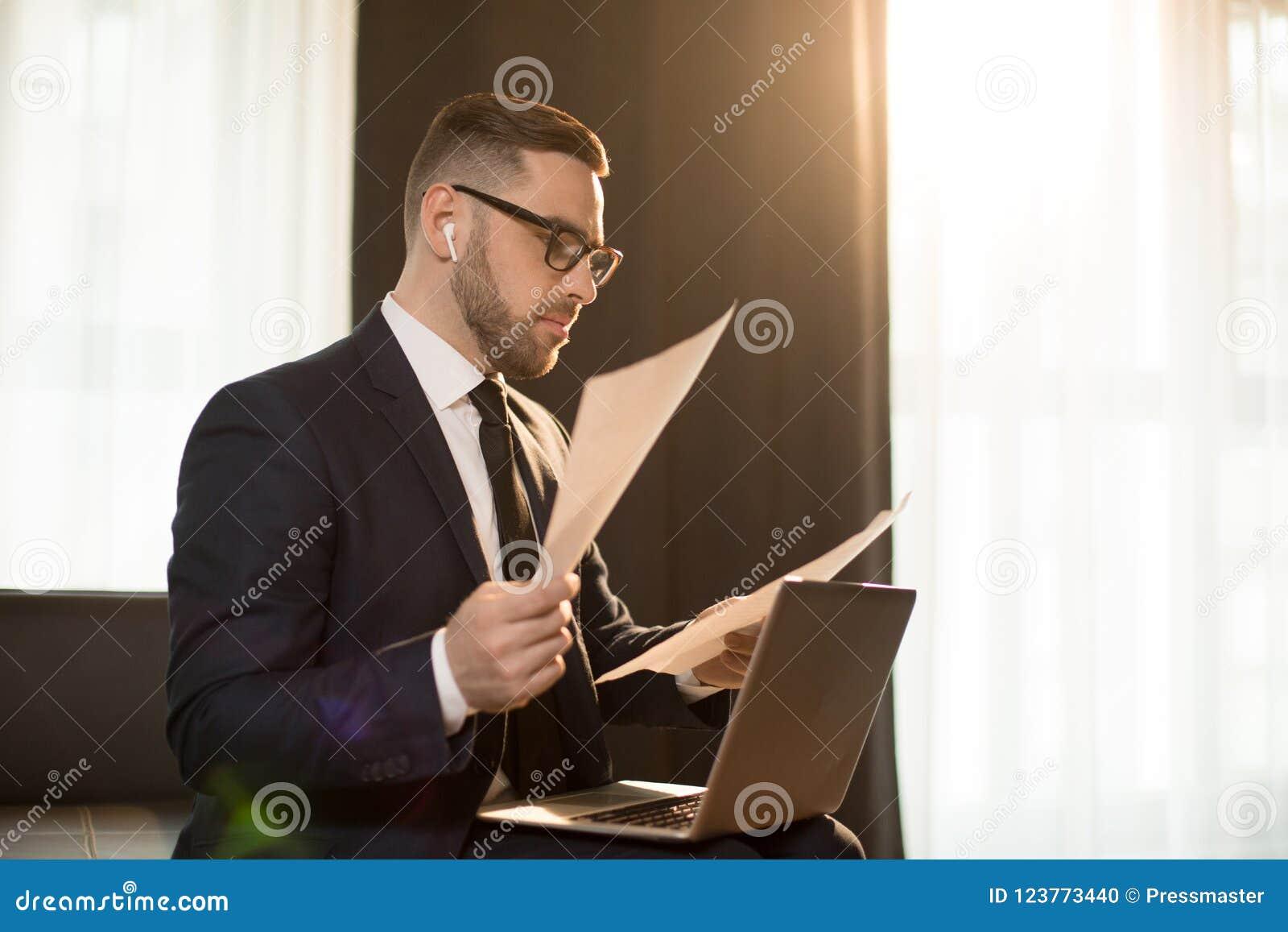 Homem de negócios moderno com papéis e dispositivos