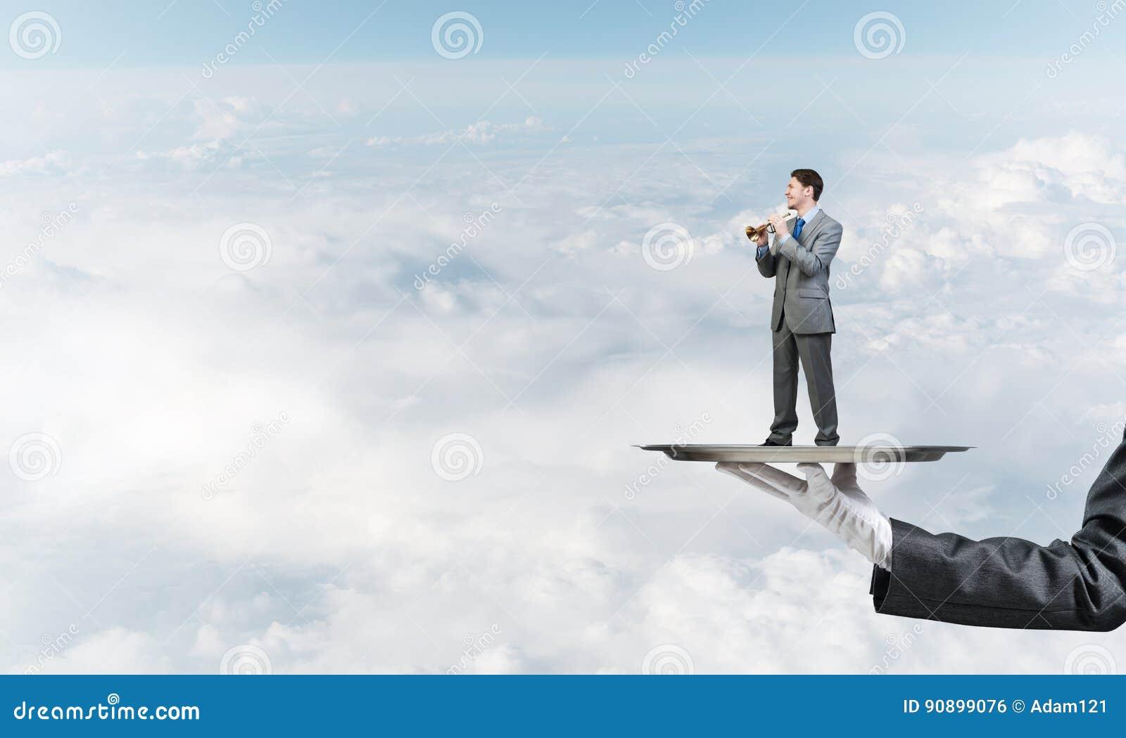 Homem de negócios na bandeja do metal que joga o pífano contra o fundo do céu azul
