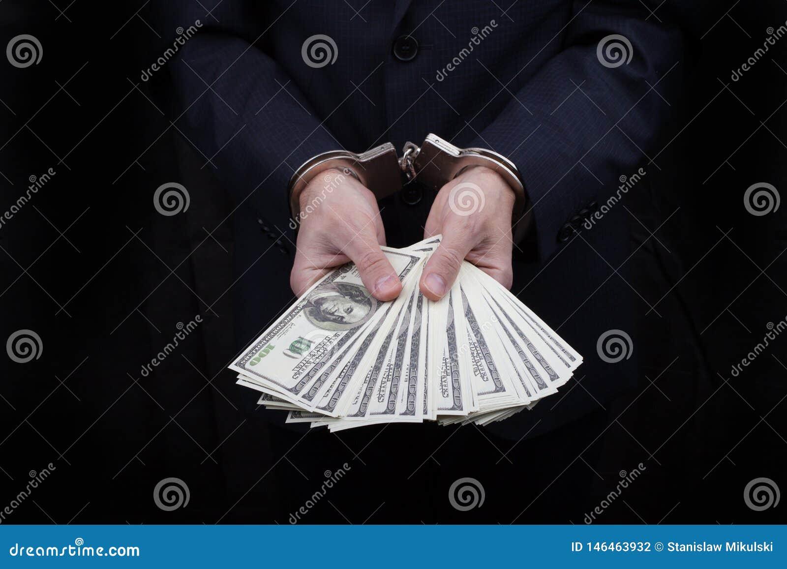 Homem de negócios nas algemas que guardam o subôrno muitos dólares das centenas