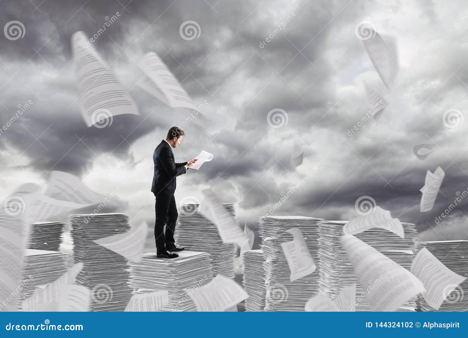 Homem de negócios no trabalho sobre uma pilha das torres de papel das folhas