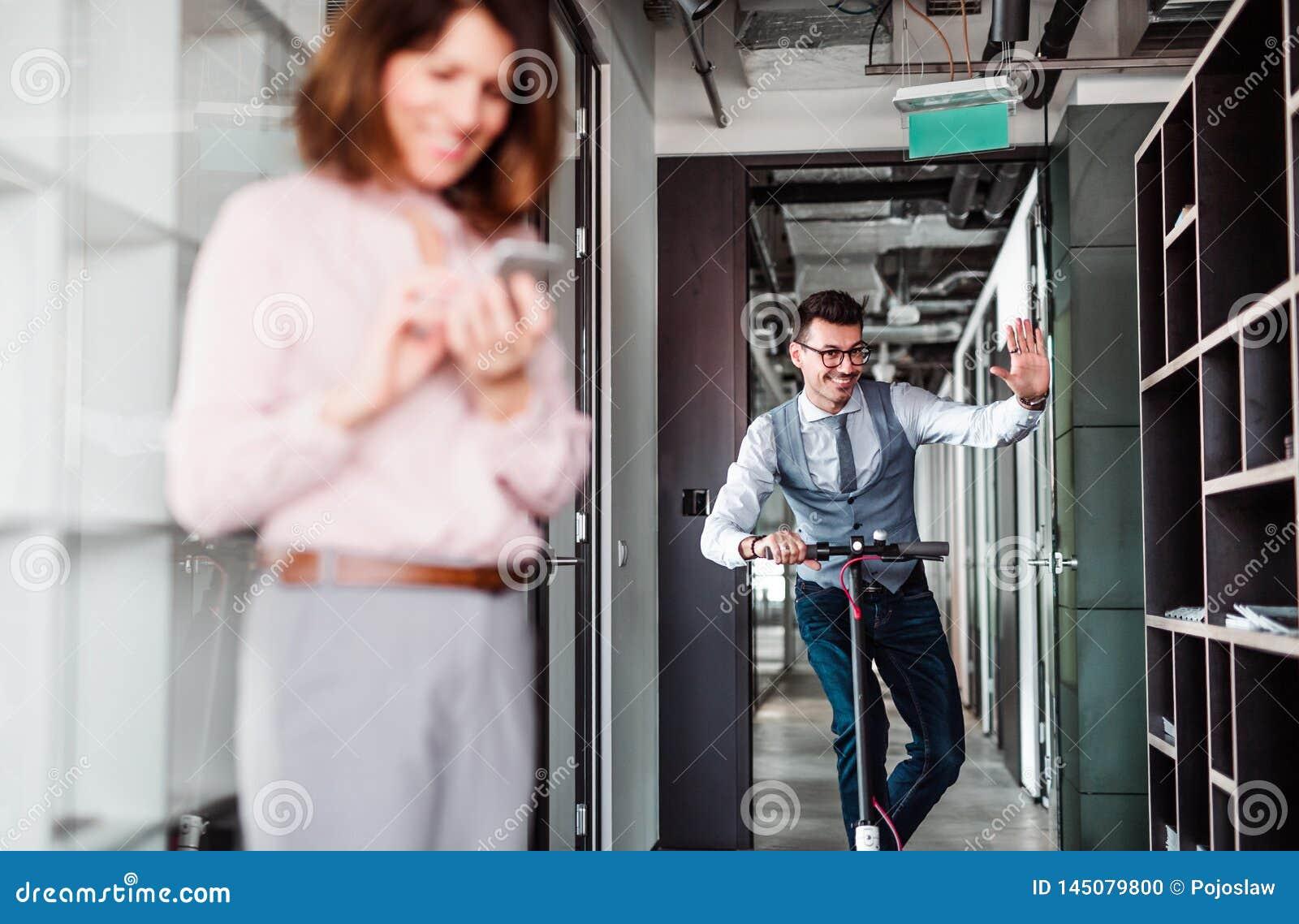 Homem de negócios novo com  trotinette  em um prédio de escritórios, tomando uma ruptura