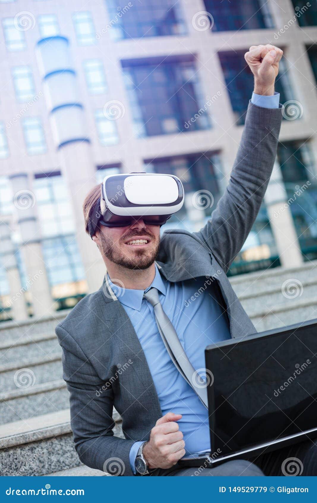 Homem de negócios novo feliz que usa os óculos de proteção de VR, sentando-se na frente de um prédio de escritórios Comemorando o