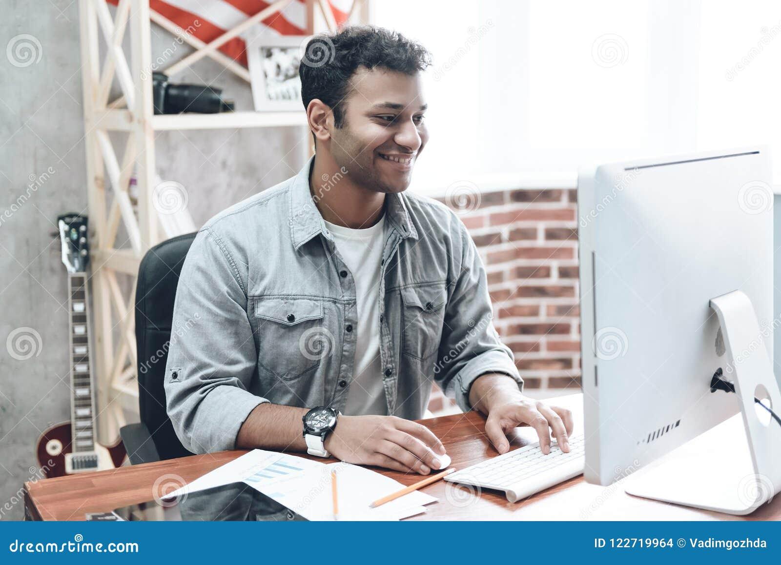 Homem de negócios novo indiano Work no computador na tabela