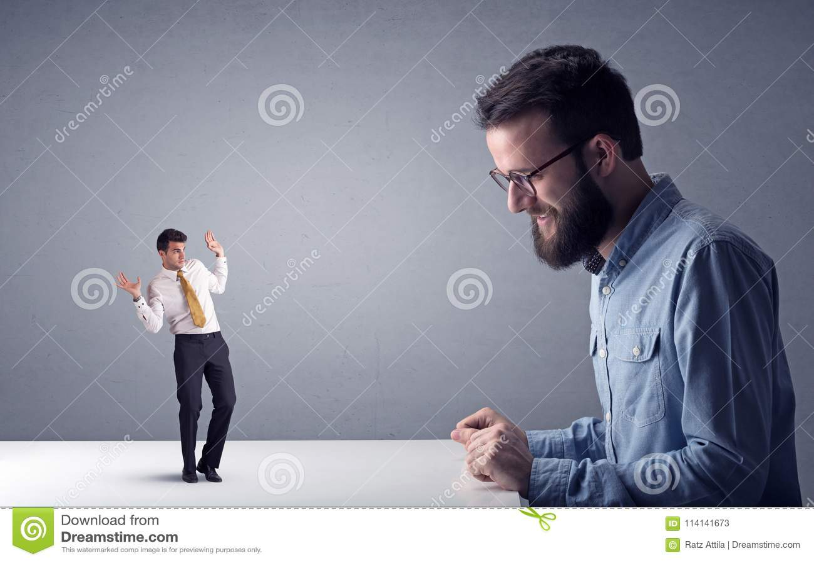 Homem de negócios novo que luta com homem de negócios diminuto