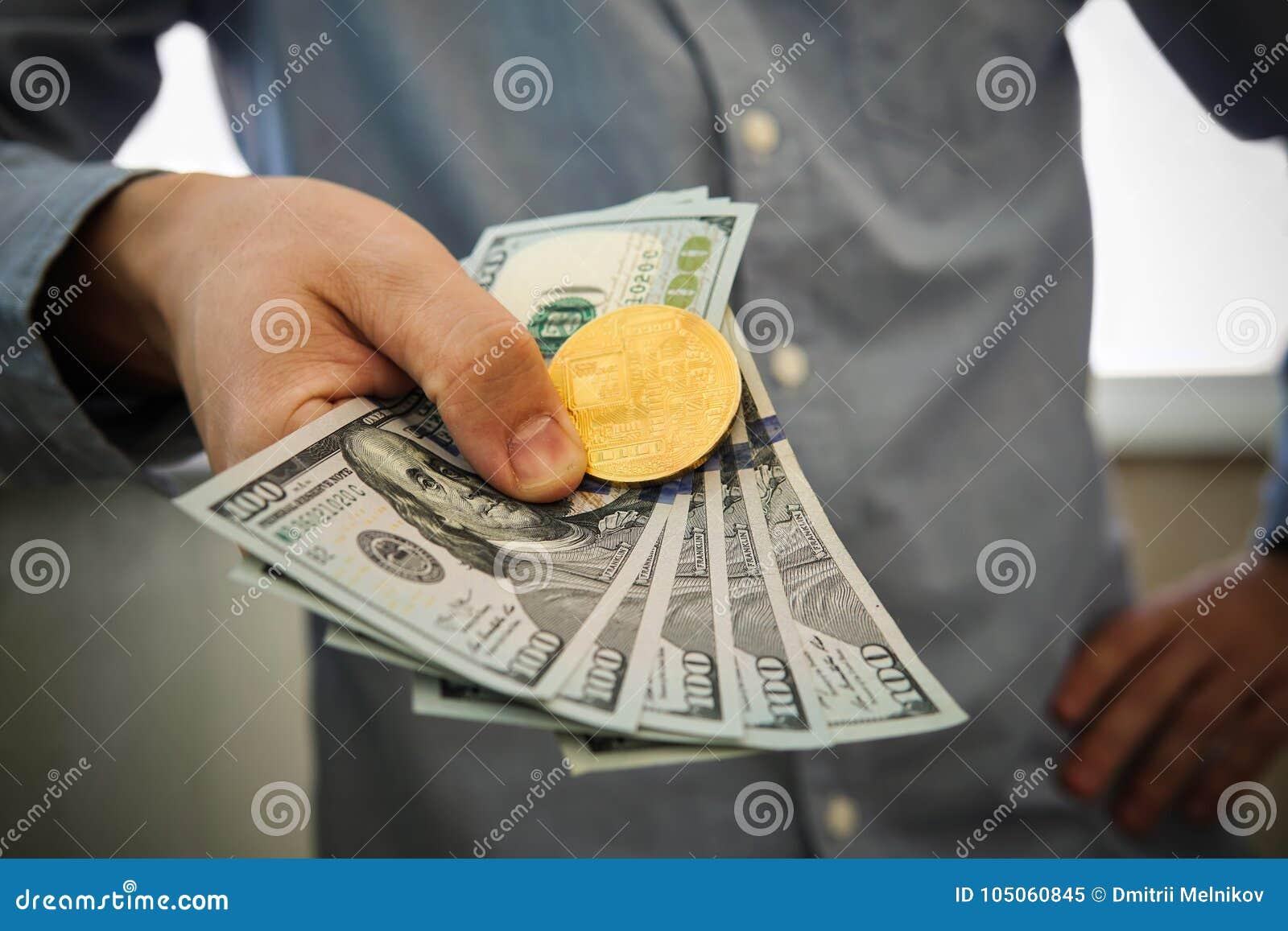 Homem de negócios novo que mantém o dólar e a moeda do bitcoin disponivéis