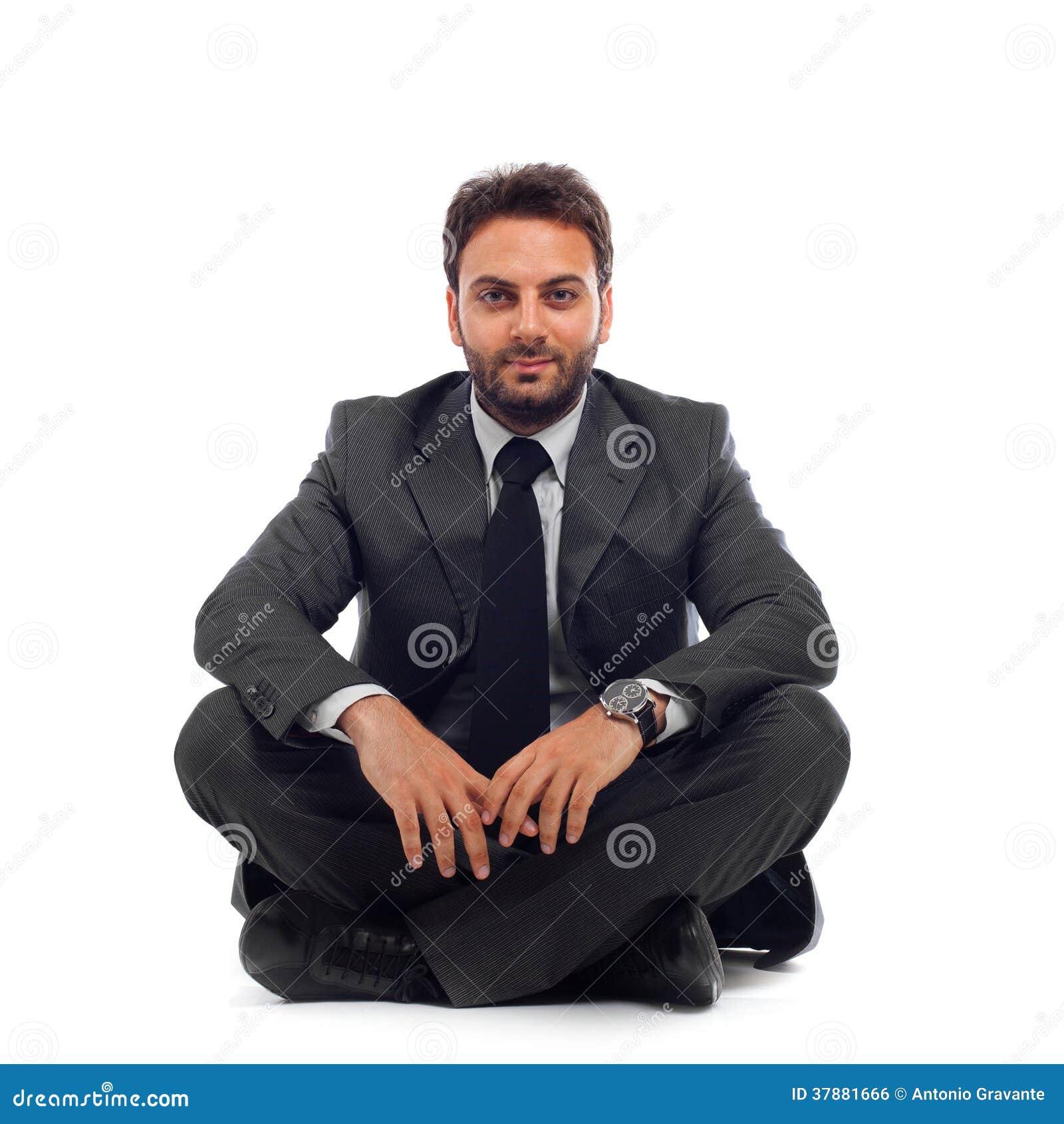 Homem de negócios novo que senta-se na terra