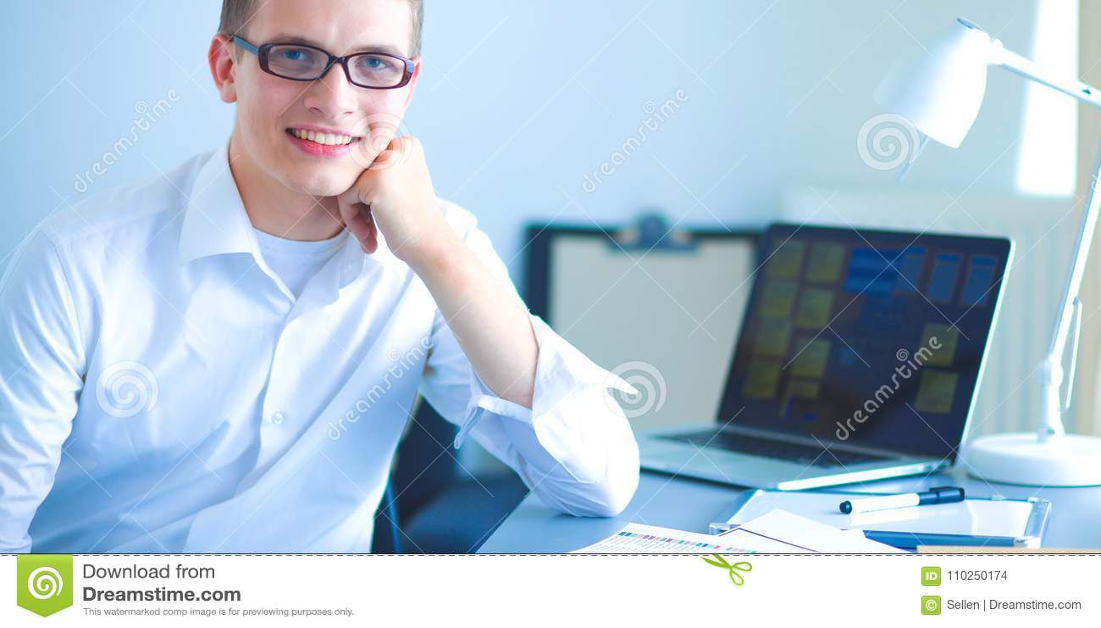 Homem de negócios novo que trabalha no escritório, sentando-se perto da mesa