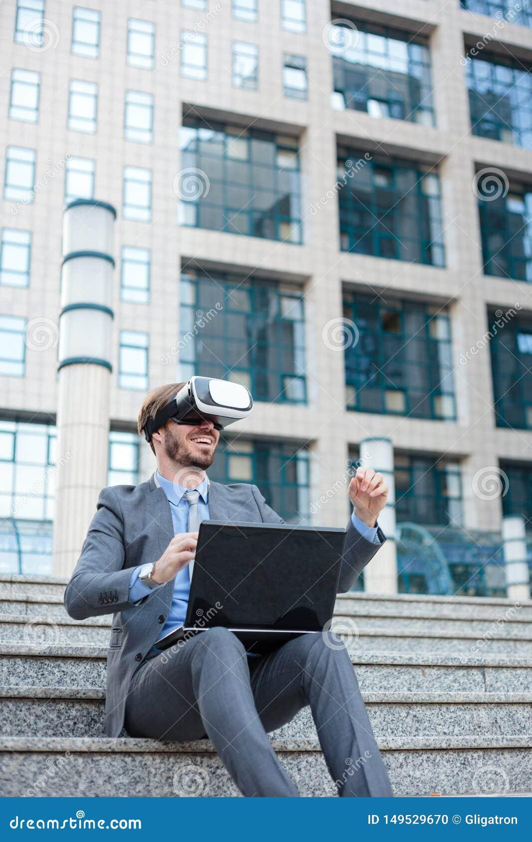 Homem de negócios novo que usa óculos de proteção de VR e fazendo os gestos de mão, trabalhando em um portátil na frente de um pr