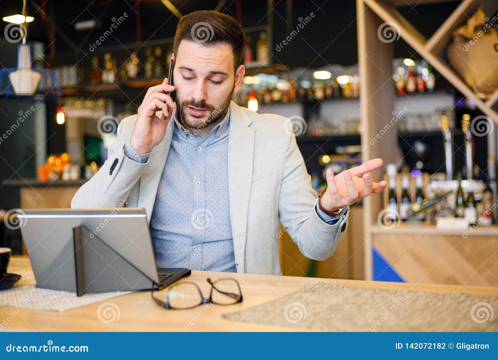 Homem de negócios novo sério que fala em um telefone, trabalhando em um café